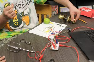 Youth using makey makey interface board with door knob and apple in order to create an innovative remote controller.